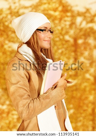Photo of pretty student girl standing in autumn park and holding books in hands, young businesswoman on golden foliage background, smiling teenager enjoying education time, fall season - stock photo