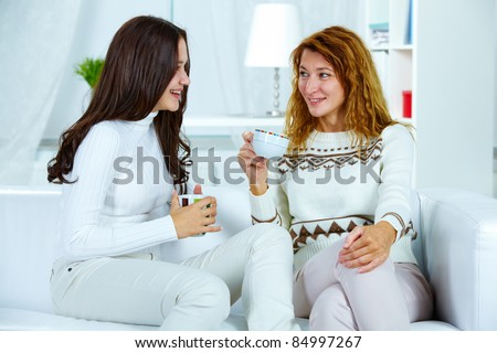 Photo of pretty woman and her teenage daughter having tea at home - stock photo