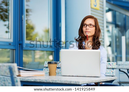Photo of pretty woman fiddling with pen and thinking over a subject while sitting in some coffee shop with her laptop. - stock photo