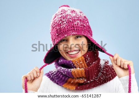 Photo of pretty woman in knitted winter cap and scarf looking at camera with smile - stock photo