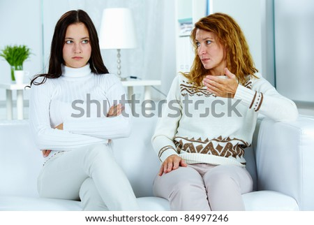 Photo of pretty woman looking at her stubborn daughter during argument - stock photo