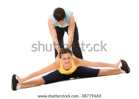 Photo of pretty young woman doing physical exercise with help of instructor