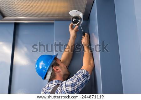 Photo Of Professional Cctv Technician Adjusting Cctv Camera - stock photo