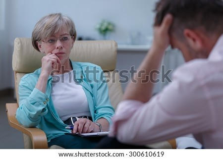 Photo of professional female therapist listening to male patient - stock photo