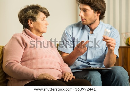 Photo of professional male carer supporting sick old woman - stock photo