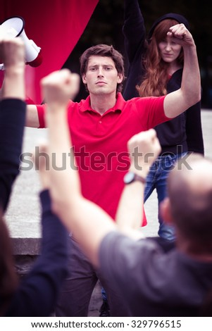 Photo of protesting man with megaphone holding fist up - stock photo