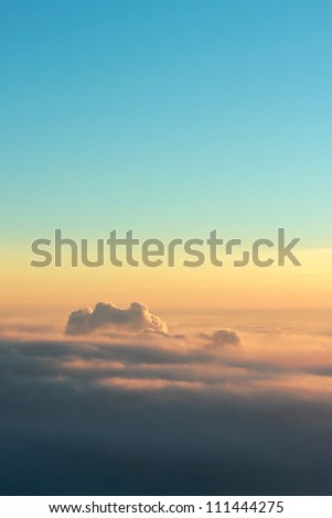 Photo of puffy clouds and blue sky from above the clouds. - stock photo