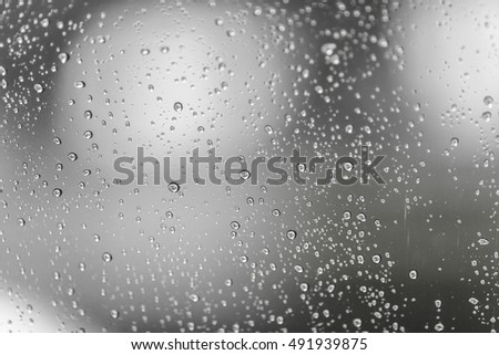 Photo of raindrops on sunroof glasses surface with cloudy background . Natural Pattern of rain drops isolated on cloudy background.