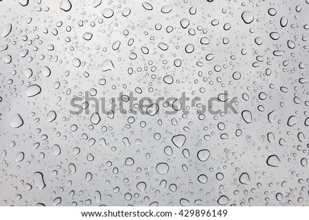 Photo of raindrops on sunroof glasses surface with cloudy background . Natural Pattern of raindrops isolated on cloudy background. - stock photo