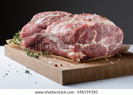 Photo of raw meat. Pork neck with herbs and green thyme on wooden board - stock photo