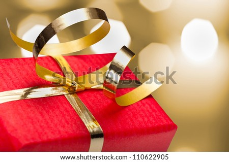 Photo of red and gold gift box with out of focus lights on a golden background - stock photo