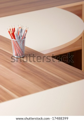 Photo of red and grey pencils in metal glass, on the table in office. - stock photo