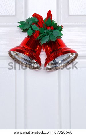 Photo of red Christmas bells with fake holly and ribbon hanging on a white door. - stock photo