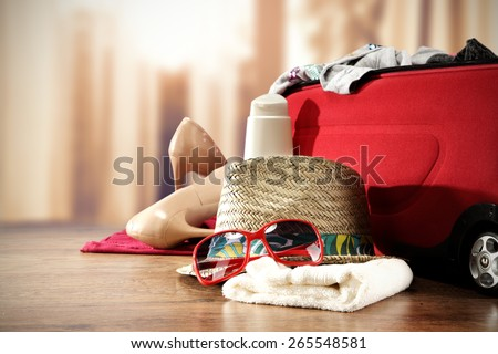 photo of red suitcase closeup and red glasses on towel hat and shoes  - stock photo