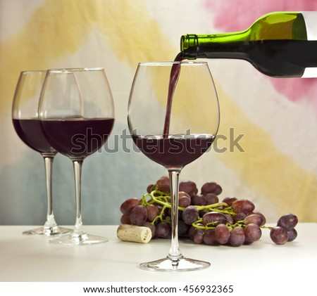 Photo of red wine being poured into glass from bottle; there are more blurred full wine glasses in the background, and also out of focus grapes and year 2014 cork; the background is abstract stains - stock photo