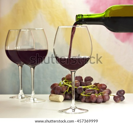 Photo of red wine being poured into glass from bottle; there are more blurred full wine glasses in the background, and also out of focus grapes and cork; the background is abstract stains - stock photo