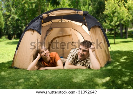Photo of resting couple lying on green grass in tent and looking at camera with smiles - stock photo