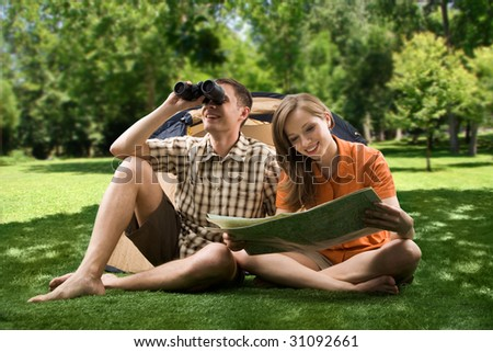 Photo of resting couple sitting on green grass while girl reading paper and guy watching through binoculars - stock photo