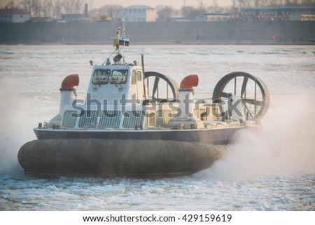 Photo of Russian ACV Hovercraft in Action on a Frosen River. Air Cushion Vehicle Blows Water on a Winter Lake - stock photo