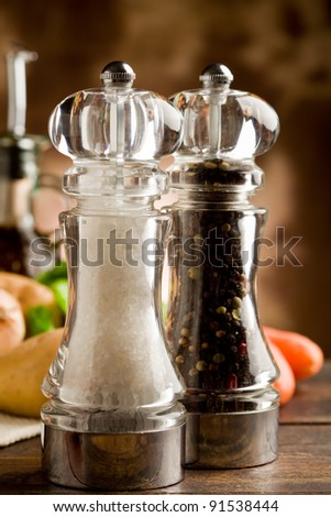 photo of salt and pepper mill with ingredients around on wooden table