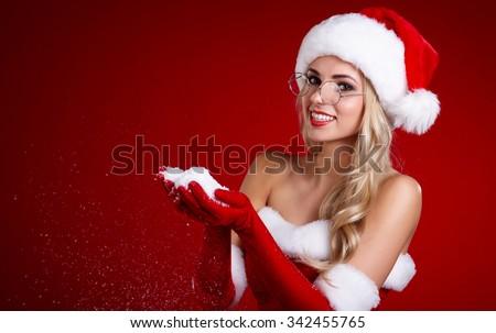 Photo of santa Christmas girl blowing snow. - stock photo
