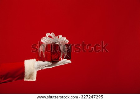 Photo of Santa Claus gloved hand with red giftbox, on a red background - stock photo