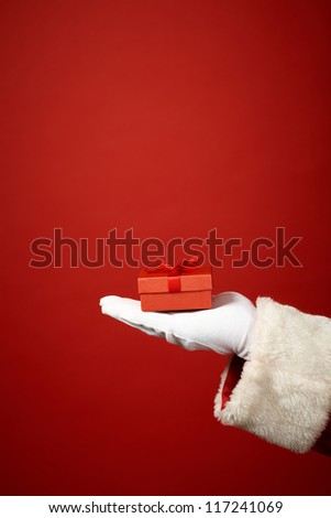 Photo of Santa Claus gloved hand with small red giftbox - stock photo