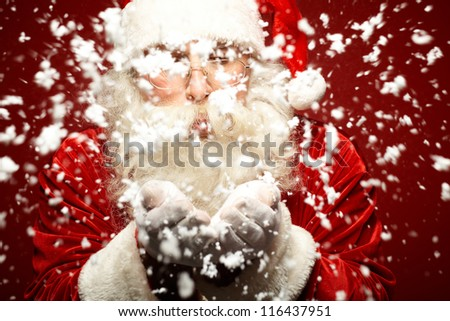 Photo of Santa Claus in eyeglasses blowing snow from his palms - stock photo