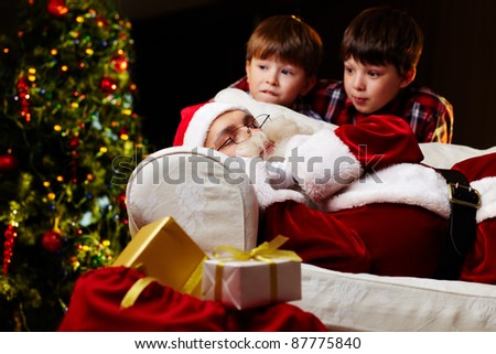 Photo of Santa Claus sleeping on sofa with two amazed kids near by - stock photo