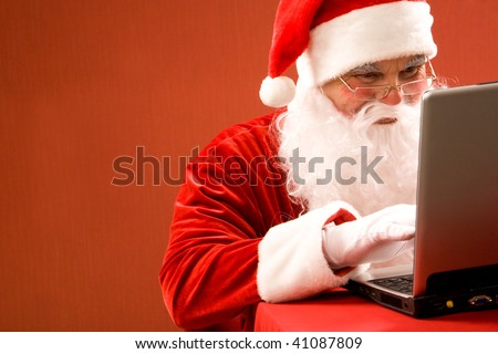 Photo of Santa Claus typing e-mail message of congratulation - stock photo