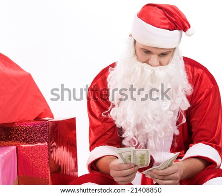 Photo of Santa sitting and counting money with pile of giftboxes near by - stock photo