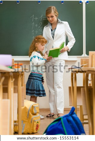 Photo of schoolgirl and teacher reading book together in the classroom - stock photo