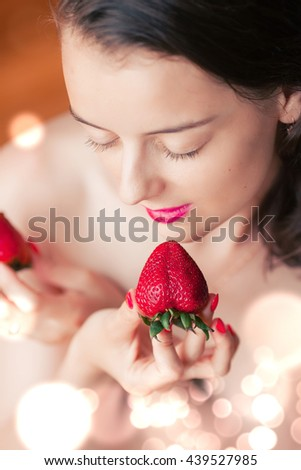 Photo of seductive female eating strawberry, closeup portrait of redhead sensual woman biting juicy fruit , fruity diet, tasty dessert, Valentine day, pleasure concept - stock photo