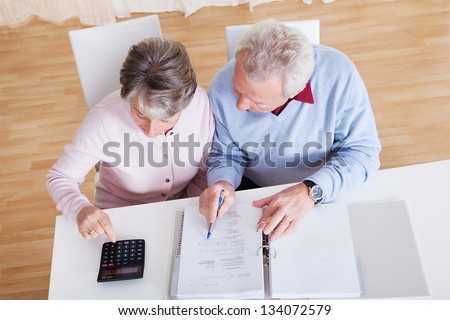 Photo of Senior Couple Calculating Budget At Home - stock photo