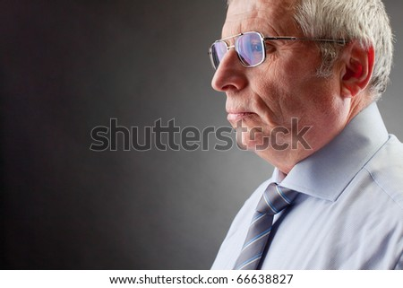 Photo of senior employer on black background - stock photo