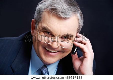 Photo of senior employer speaking by mobile phone on black background - stock photo
