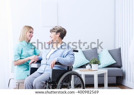 Photo of senior lady on wheelchair and her caregiver - stock photo