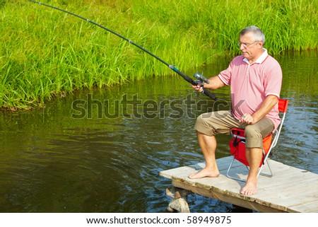 Photo of senior man fishing on weekend - stock photo