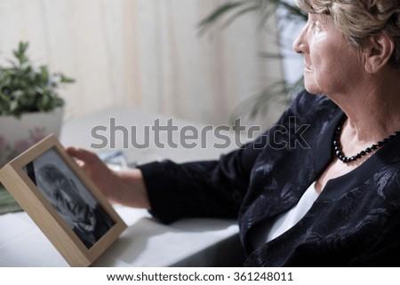 Photo of senior widow reminiscing her dead husband - stock photo