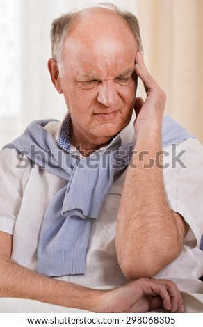 Photo of senior worried man with terrible headache