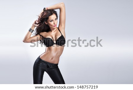 Photo of sensual beautiful woman looking at camera, posing in black bra. - stock photo