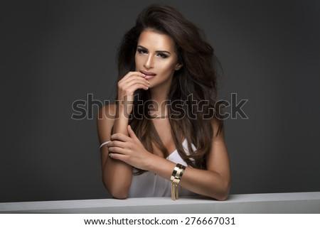 Photo of sensual beautiful woman looking at camera, posing in white top.  - stock photo