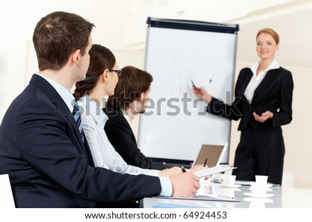 Photo of serious business people listening to female manager pointing at whiteboard while presenting new project - stock photo
