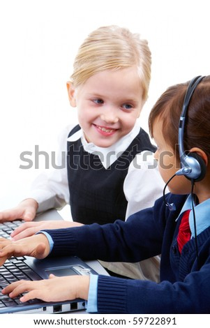 Photo of serious girl with headset typing and talking to her friend