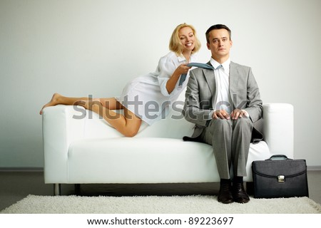 Photo of serious man sitting on sofa with seductive laughing woman holding him by tie - stock photo