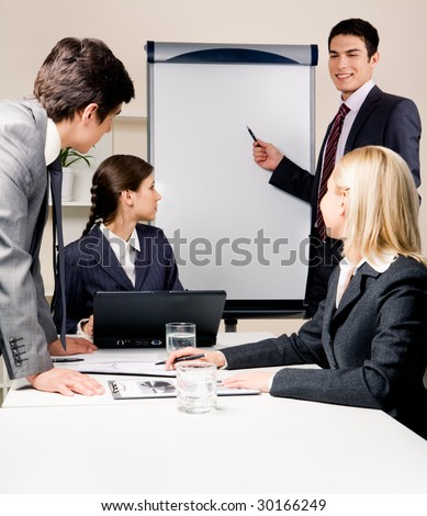 Photo of serious partners listening to successful businessman reading lecture to them during training