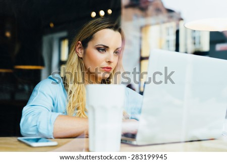 Photo of serious woman working on laptop at cafe - stock photo