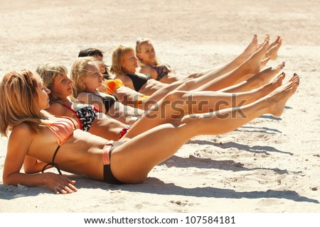 Photo of several girls in bikini lying on sandy beach and tanning in the bright summer sun - stock photo
