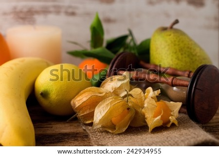 Photo of several pieces of gooseberry fruit on jute cloth with sandglass, pear, mandarin, lemon and banana in background placed on old wooden board. - stock photo