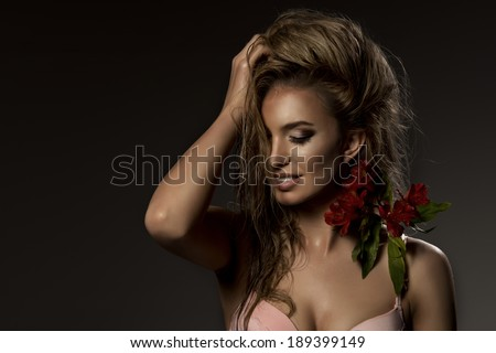 Photo of sexy blonde young girl with flower, smiling.  - stock photo